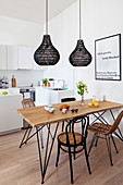 Dining table and various chairs below black pendant lamps in open-plan kitchen