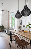 Dining table and various chairs below black pendant lamps in open-plan interior