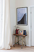 Books on rustic console table below picture on wall