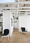 Wooden roof structure, partition walls and black chairs in open-plan interior