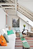 Weißes Sofa mit bunten Kissen und rustikale Holzbank als Couchtisch im Wohnzimmer