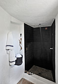 Shower area with black tiles in white bathroom