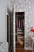 Flamingo-patterned wallpaper on wall and door into walk-in wardrobe
