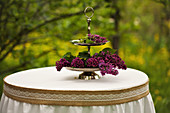 Purple lilac on cake stand on table with ornate tablecloth in garden