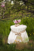Ornate tablecloth and peonies on round table below tree