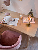 Christmas decorations, magazine and lamp on desk with shell chair
