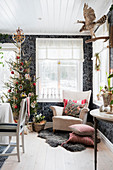 Armchair and Christmas tree against black patterned wallpaper