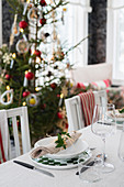 Festive place settings on dining table in front of Christmas tree