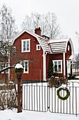 Falu-red Swedish house in snowy garden