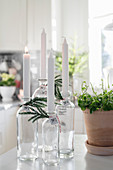 DIY candlesticks made from glass bottles decorated with fir sprigs