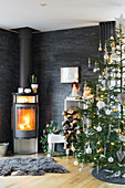 Fireplace and Christmas tree in living room with slate-clad walls
