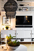 White sideboards, TV and shelves in living room