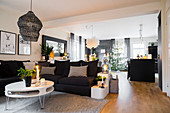 Sofa and round coffee table in open-plan interior with Christmas decorations