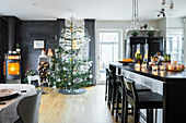 Elegant island counter, Christmas tree and fireplace in open-plan interior