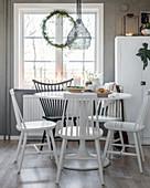 Windsorstühle in Schwarz und Weiß am Esstisch vor dem Fenster