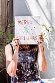 Woman holds Christmas greeting in front of her face