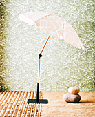 Parasol with umbrella stand and natural stones in front of wallpapered wall