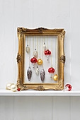Vintage Christmas-tree baubles hung in gilt picture frame