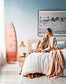 Young woman sitting on bed in bedroom in beach look