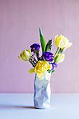 Frühlingsblumen in einer Vase in Form einer zerdrückten Dose