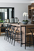 Tall black stools at wooden kitchen counter