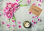 Tasse Kaffee daneben rosa Tulpenblüten und -blätter sowie Schild mit Aufschrift 'Happy'