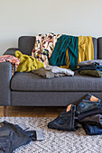 Clothing on a grey upholstered sofa