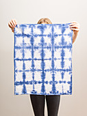 A woman holding a tea towel dyed using the shibori technique