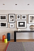 Gallery of black-and-white pictures above console table in hallway