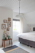 Double bed, vases on stool and collection of pictures on wall in attic bedroom