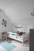 White, child's bed in attic nursery