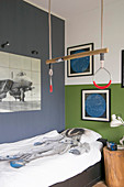 Gymnastic rings in child's bedroom with blue wall and green-and-white wall