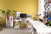 Two desks on trestles against yellow wall