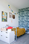 Grey metal bed against blue-patterned retro wallpaper in child's bedroom