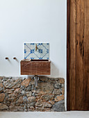 Wooden sink mounted on wall above stone wall