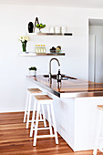 Two stools at white island counter with wooden worksurface and sink