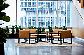Elegant leather chairs, table and house plants in lobby with glass wall