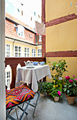 Folding table, chair, potted plants and washing lines on balcony with yellow side wall