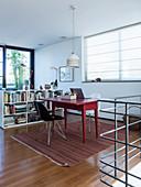 Zwei Stühle um einen roten Tisch als Schreibtisch