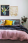 Picture and macrame over the bed with various boho-style pillows