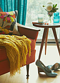 Orange armchair, shoes and side table