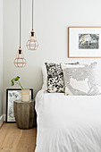 Two pendant lamps above bedside table against grey wall