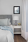 Bed with grey headboard and white bedside table in bedroom