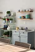 Kitchen base unit, crockery on wall shelves and houseplants on metal shelving unit