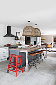 Kitchen counter and barstools in open-plan vintage-style kitchen