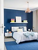 Doppelbett im Schlafzimmer mit blauer Wand und blauem Teppich