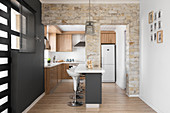 Stone wall with two openings leading into open-plan kitchen