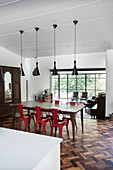 Wooden dining table and red chairs below pendant lamps with view onto terrace in background