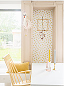 Branch in picture frame on wallpaper with gold polka-dots next to faux swan head on door frame