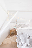 Double bed and garland handmade from white-sprayed leaves in white bedroom
